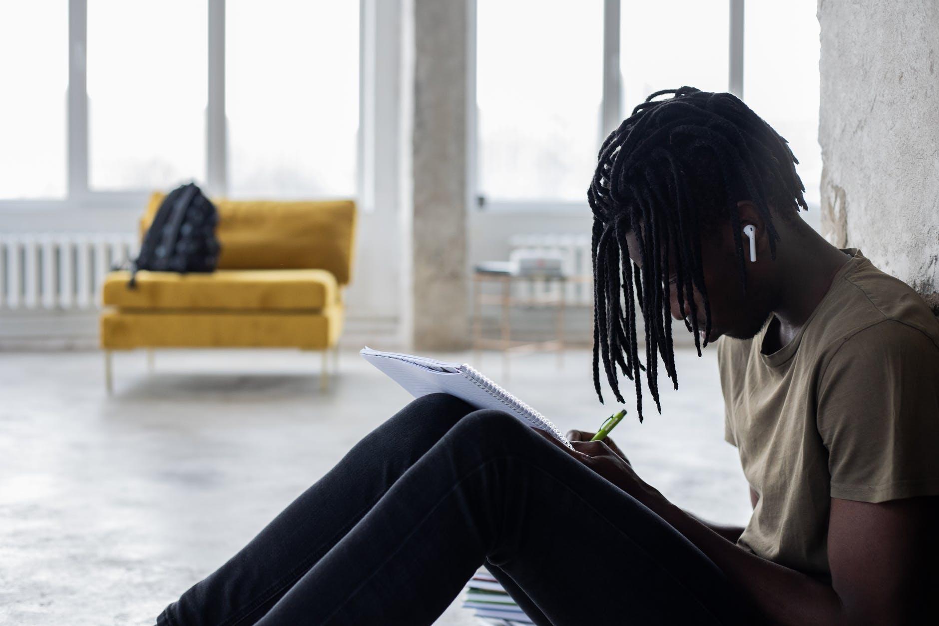 black man in tws earbuds writing in notebook