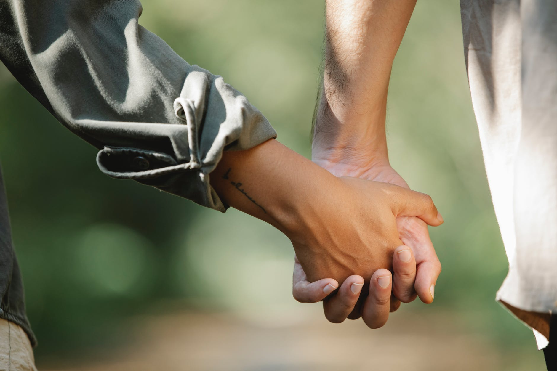 unrecognizable couple walking in park holding hands