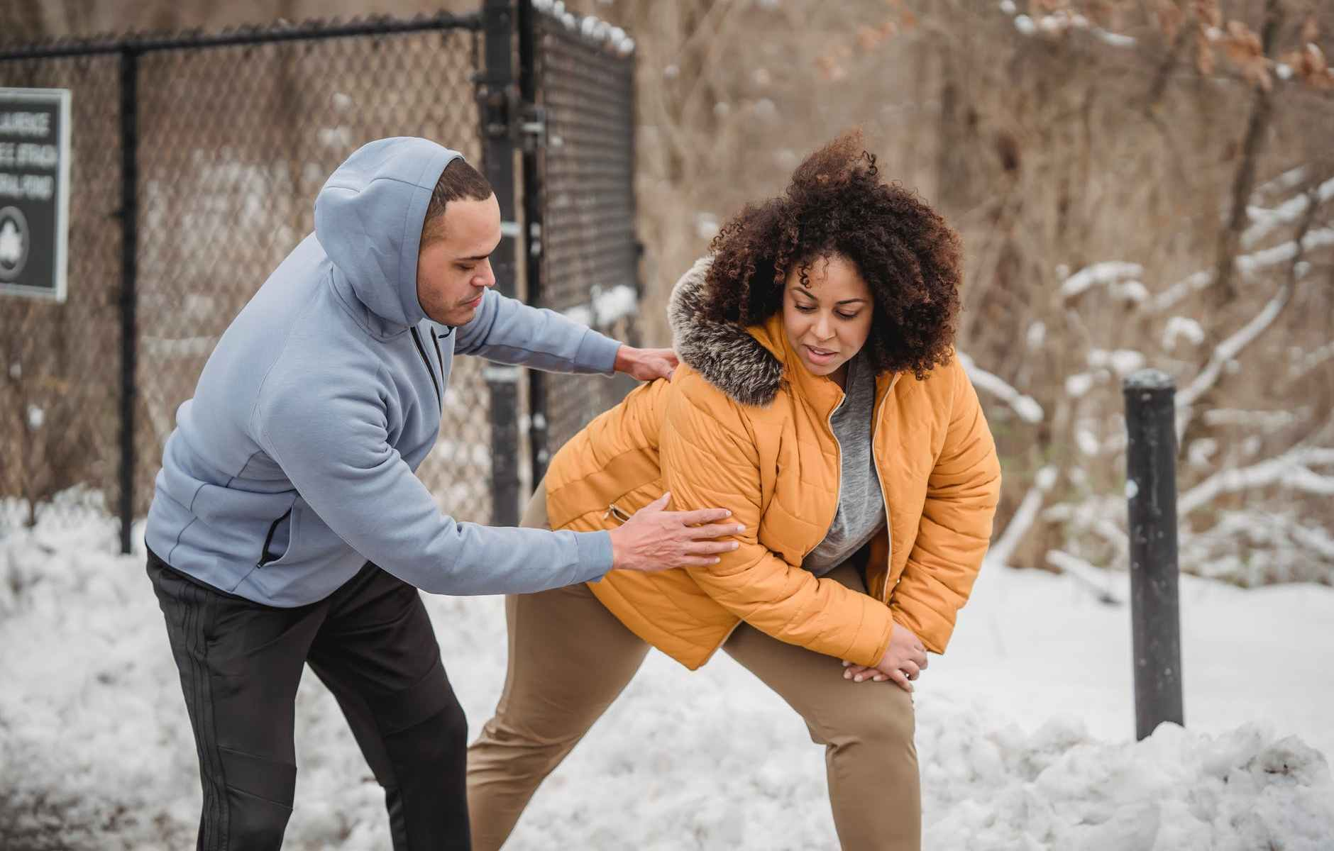 caring black coach helping plump african american woman to do exercise