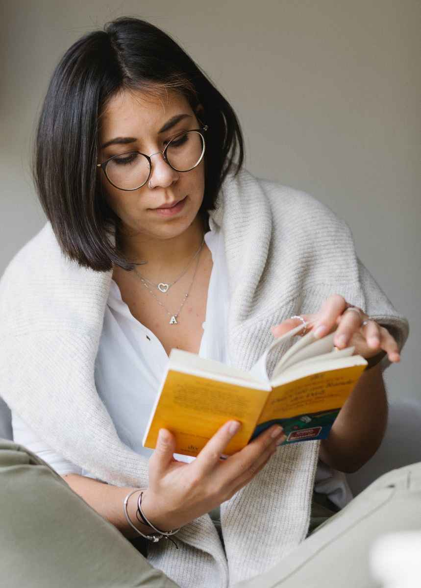 serious young female reading interesting story on couch