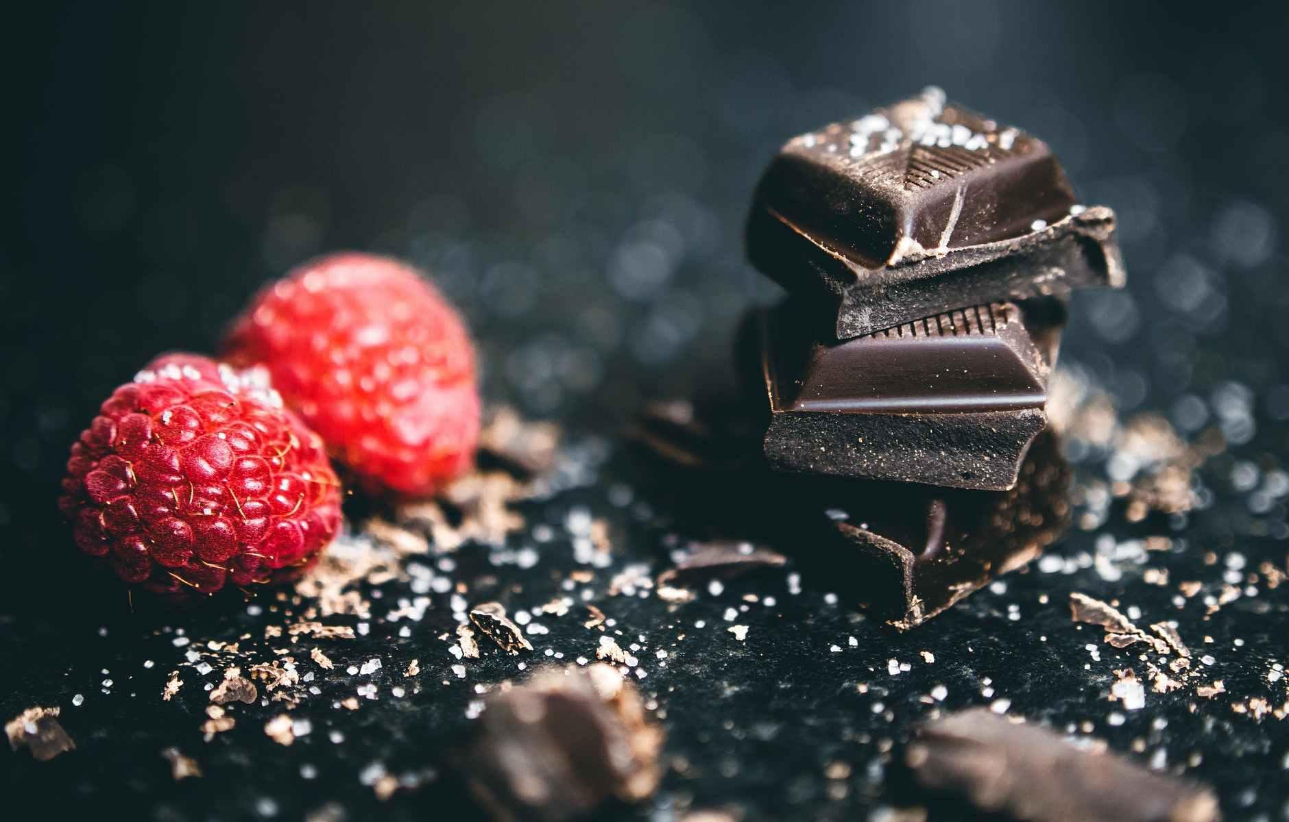 close up photo of stacked chocolates bars beside raspberries