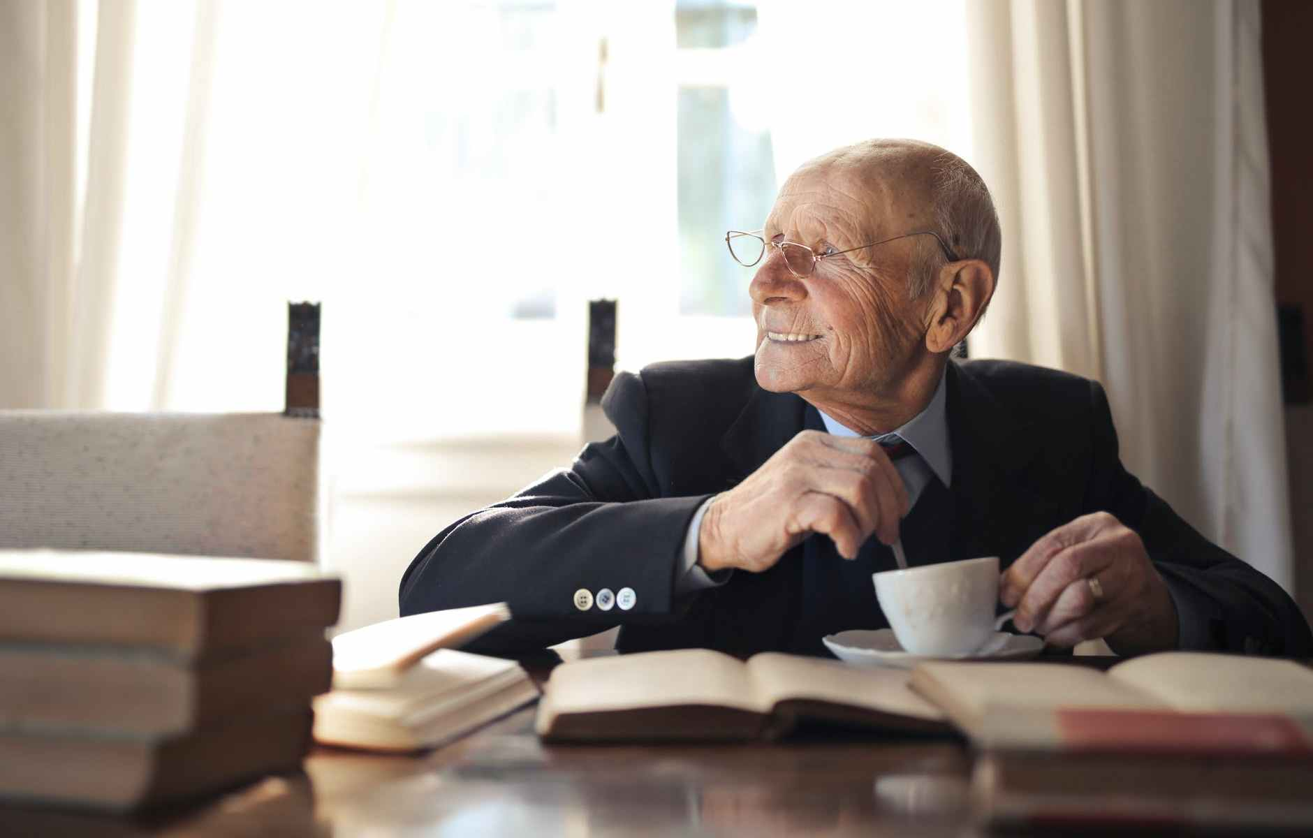 senior man drinking hot beverage while sitting at table with books