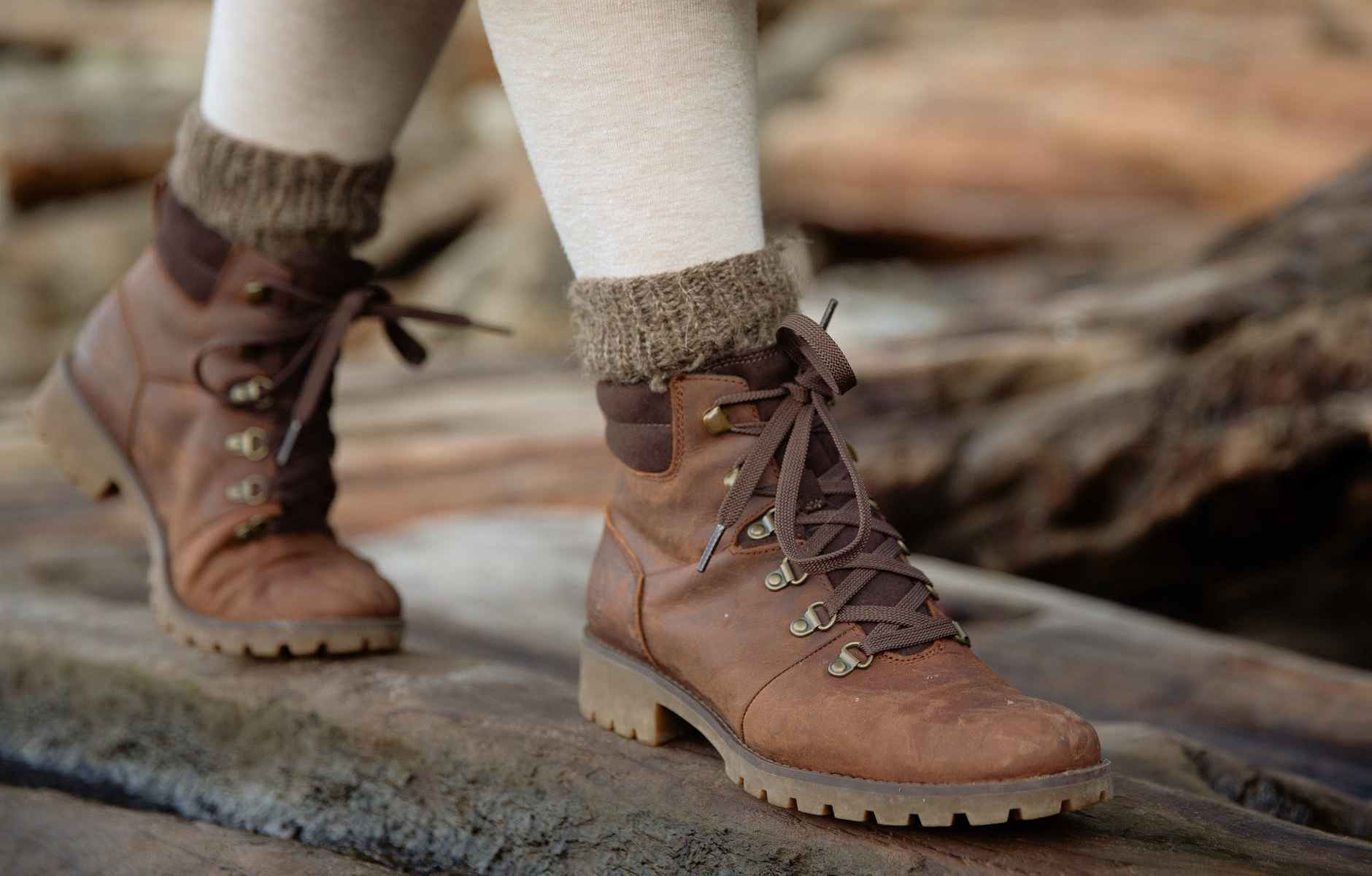 crop person in autumn boots walking on wet wooden logs