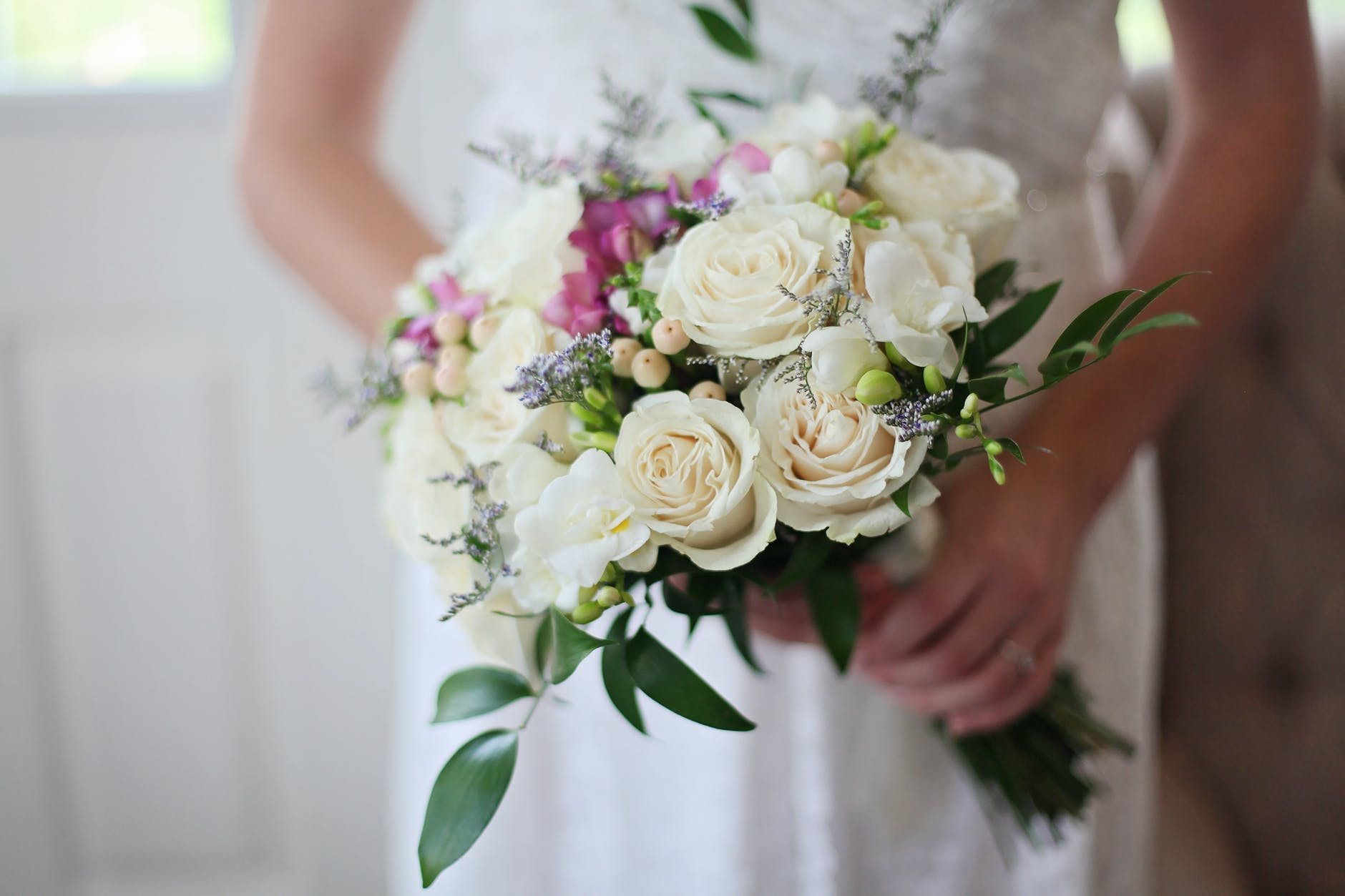 brides holding white bouquet of roses