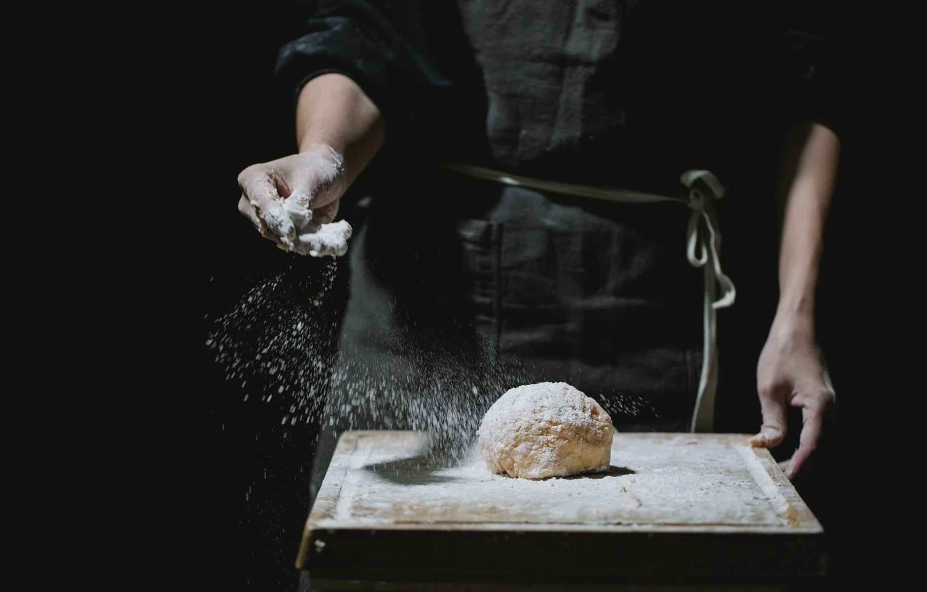 cook sprinkling flour on dough for pastry