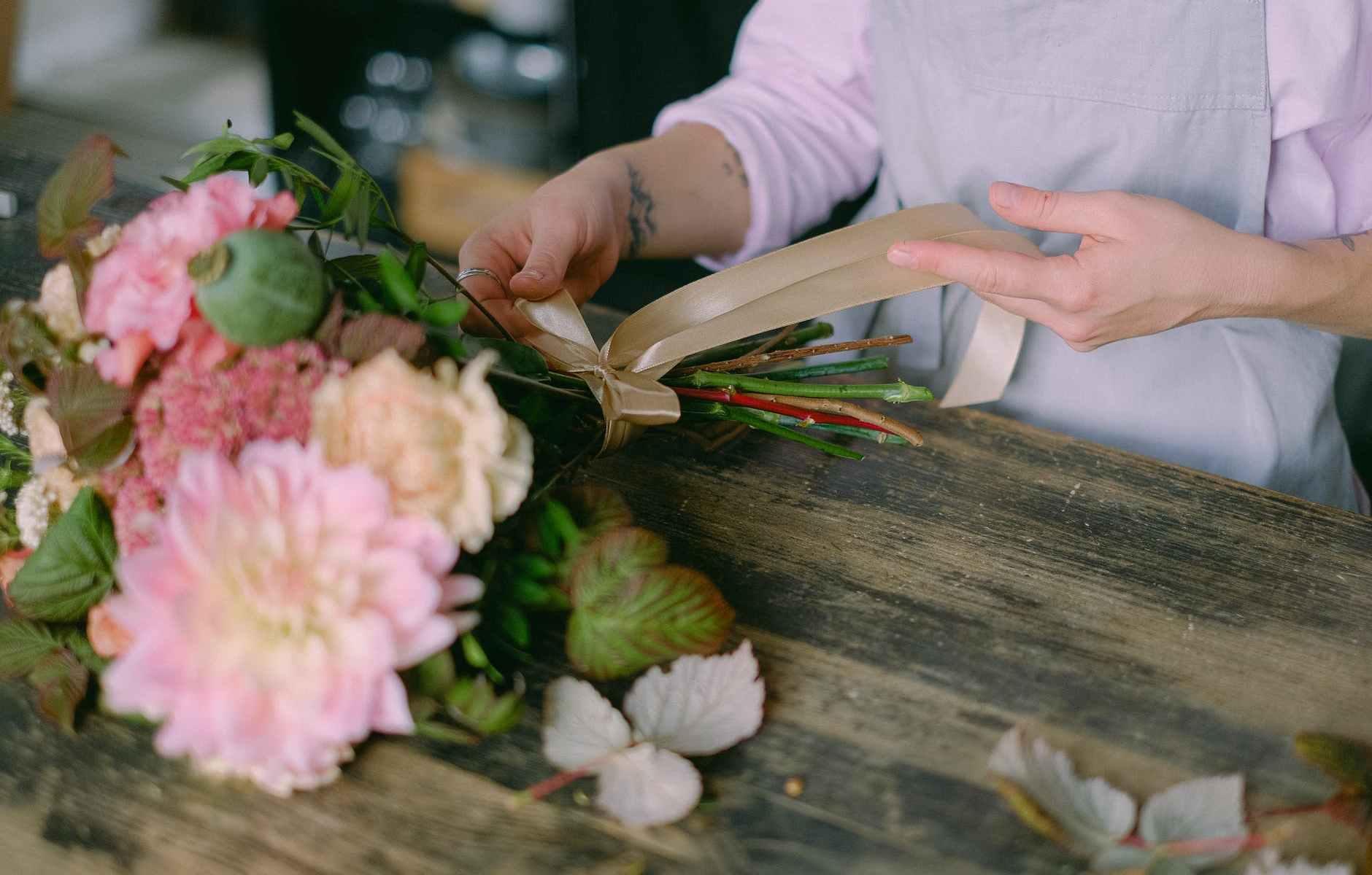 person arranging bouquet of flowers