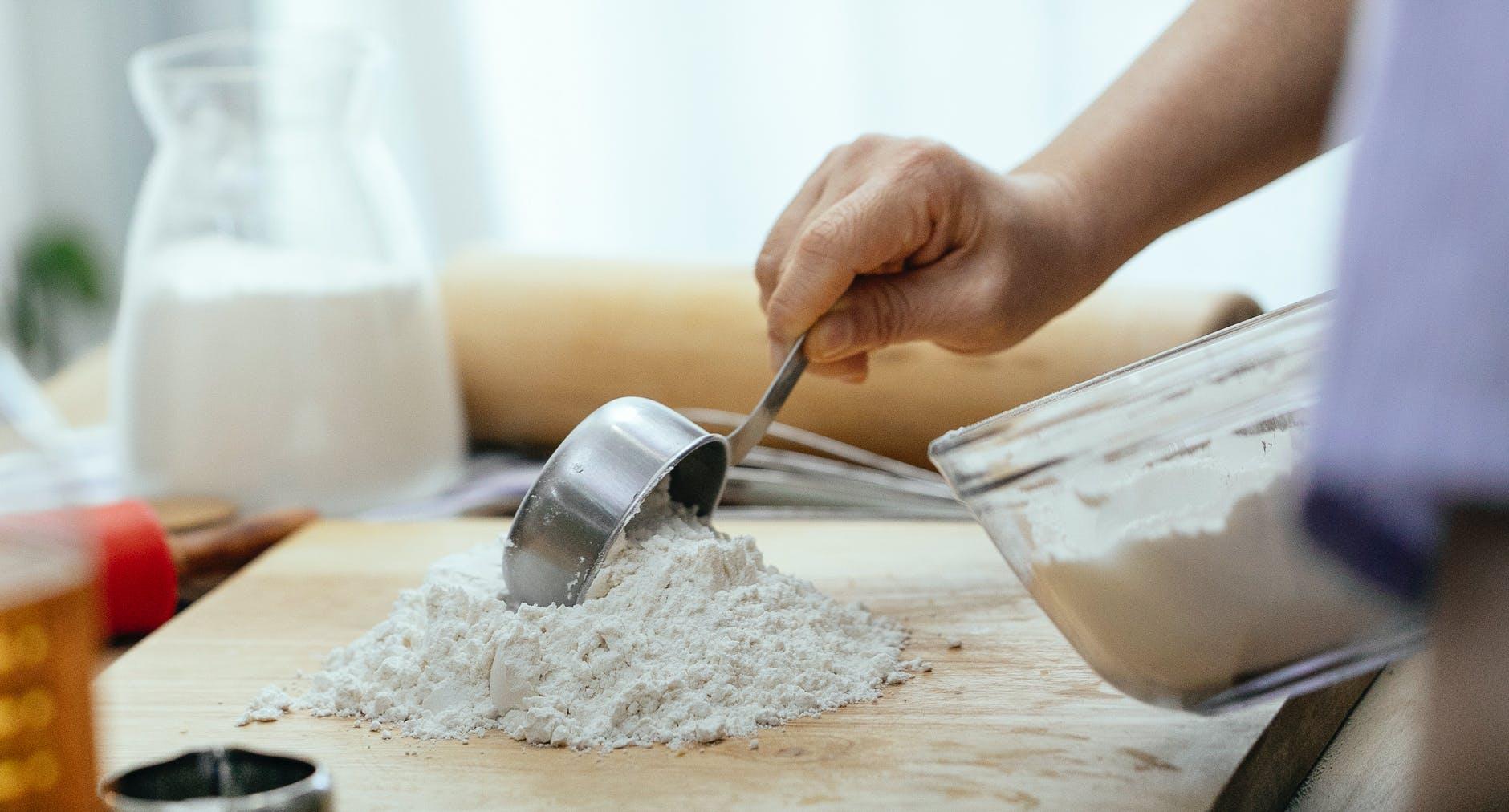 crop adult woman adding flour on wooden cutting board