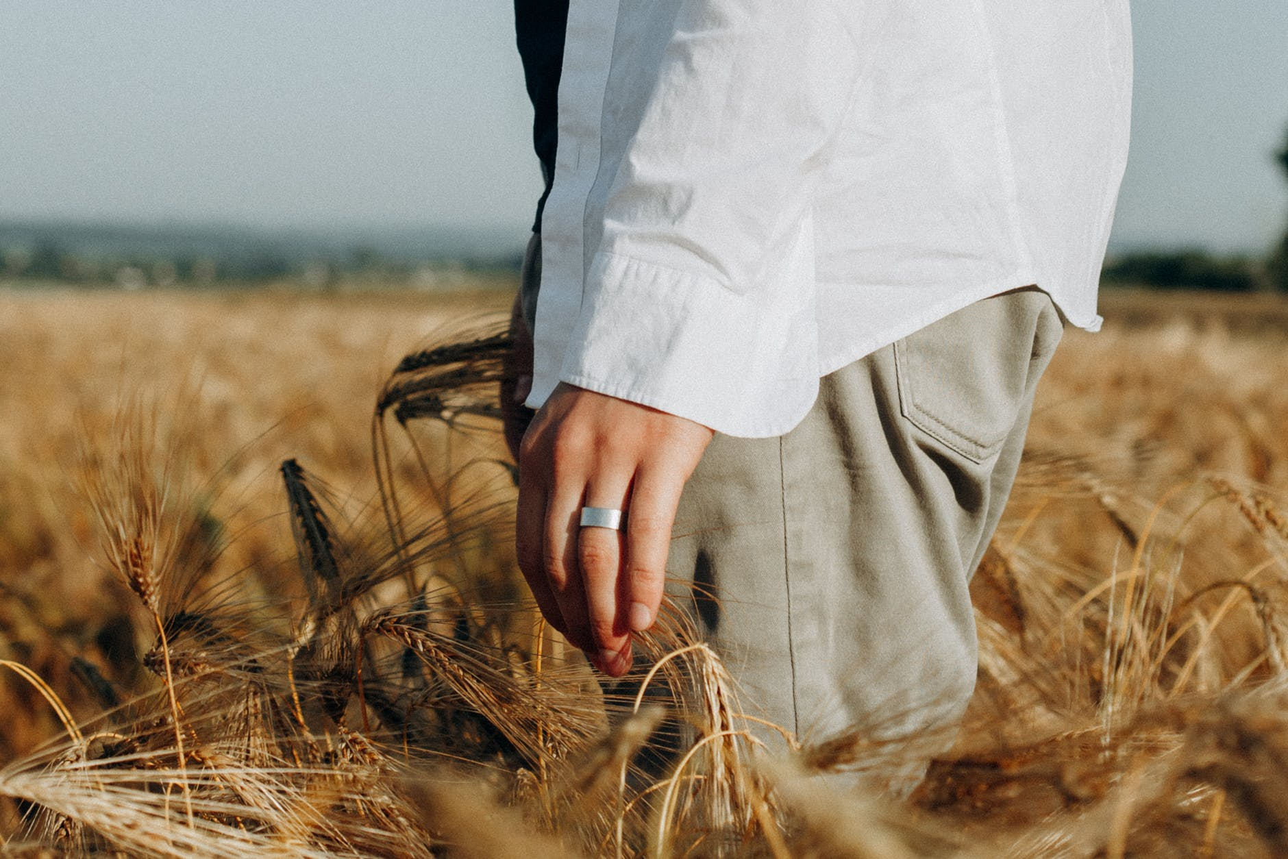close up photo of person standing on wheat field