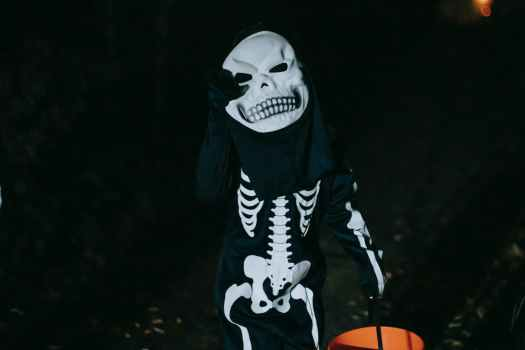unrecognizable kid in skeleton costume during halloween