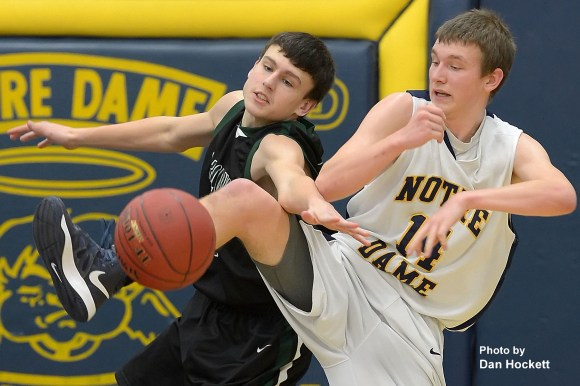 Photo by Dan HockettWest Burlington's Kyle Rokosz (left) and Notre Dame's Matt Burford (right) battle for a loose ball during Friday night's game in Burlington. Notre Dame defeated West Burlington, 64-14.