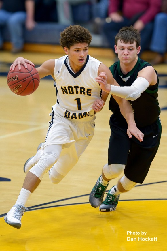 Photo by Dan Hockett Notre Dame's Xavior Williams (1) drives to the lane while guarded by West Burlington's Jarod Fogle Friday night in Burlington. Notre Dame defeated West Burlington, 63-54.