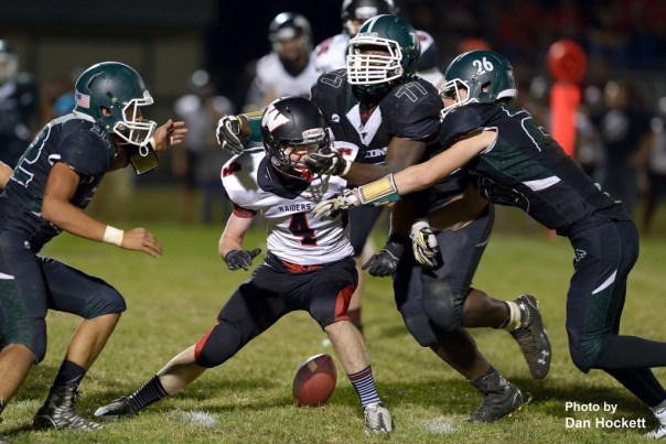 Photo by Dan Hockett West Burlington – Notre Dame's Shavontae Nelson (77) and Tanner Snodgrass (26) strip the ball from Williamsburg Running Back Michael Galyon (4) Friday night in West Burlington. Williamsburg defeated the Falcons, 48-12.