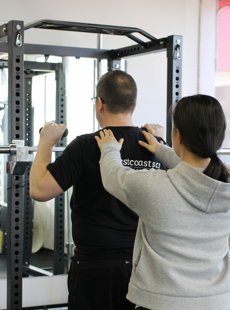 kinesiologist helping client with exercise