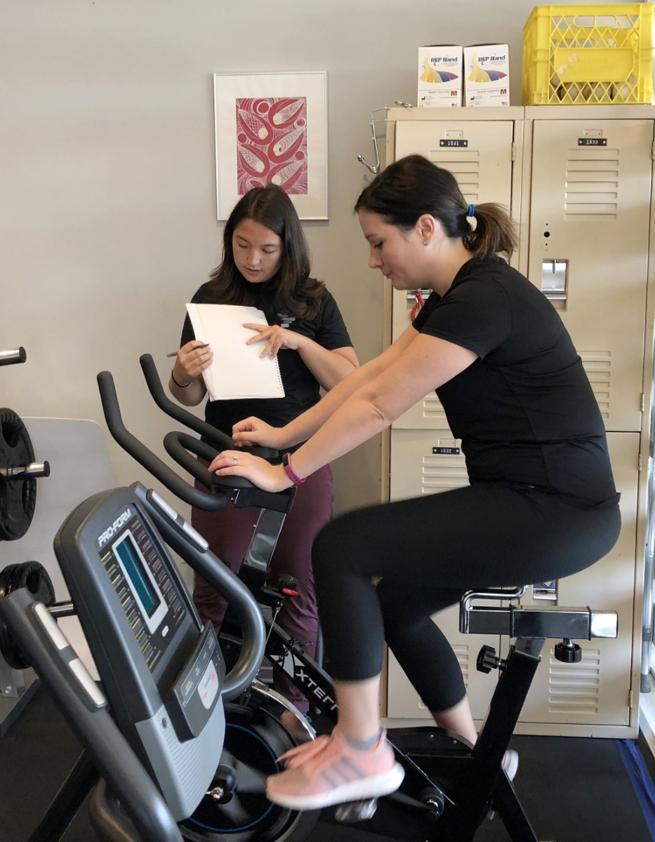 kinesiologist assisting client with exercise