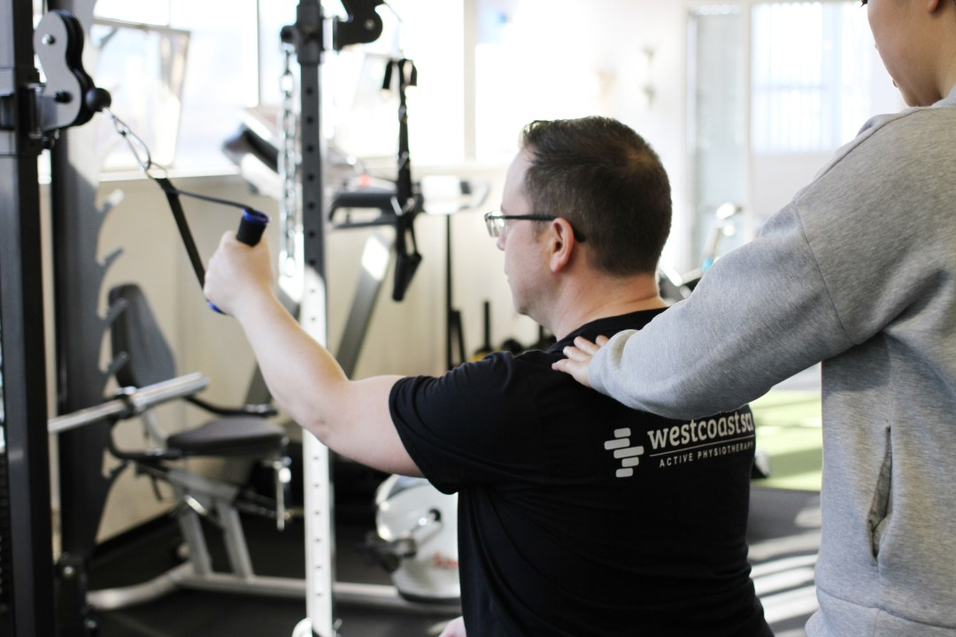 personal trainer kinesiologist assisting client with workout