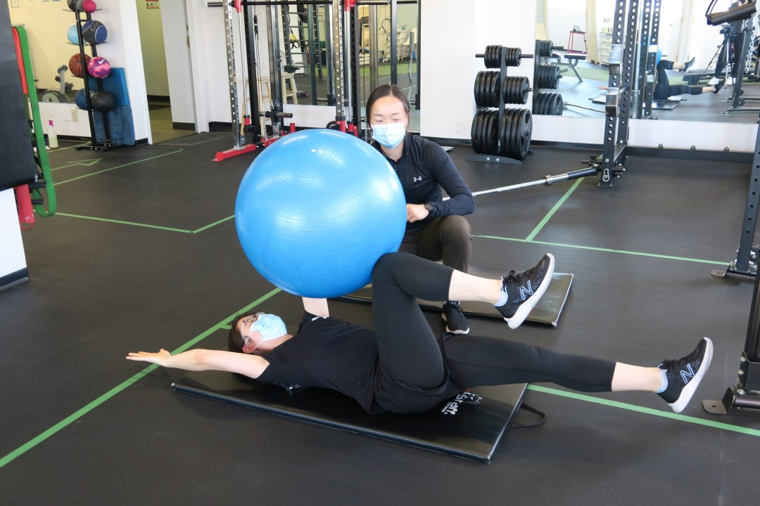 Personal Trainer Kinesiologist supervising client with dead bugs exercise with exercise ball
