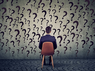 Seated man surrounded by questions marks.