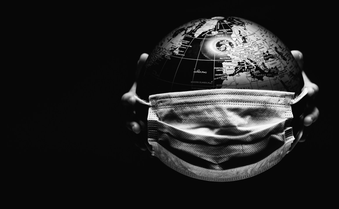 Hands holding globe isolated on black background. COVID 19 or ecological disaster concept