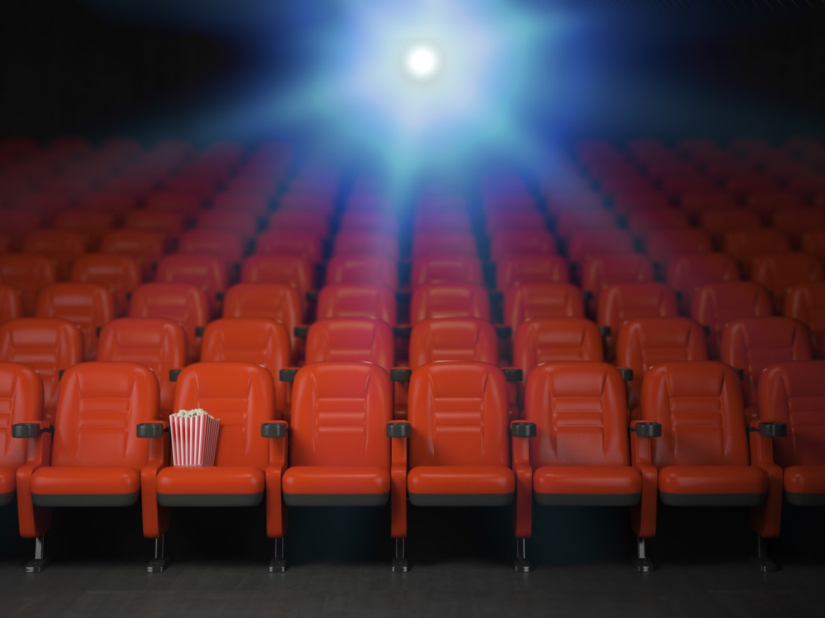 Cinema and movie theater concept background. Empty rows of red seats with pop corn.