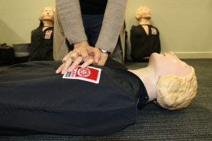A St John's Ambulance worker demonstrates chest compressions on a training mannequin.