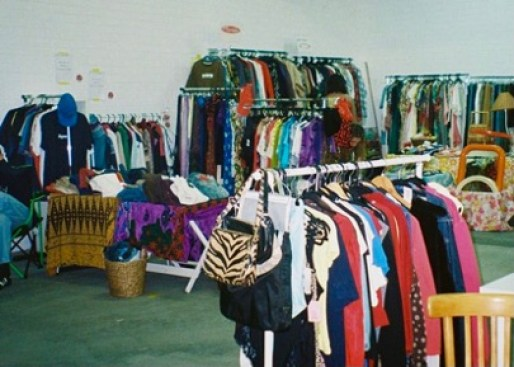 A cluster of clothing racks with second-hand pieces.