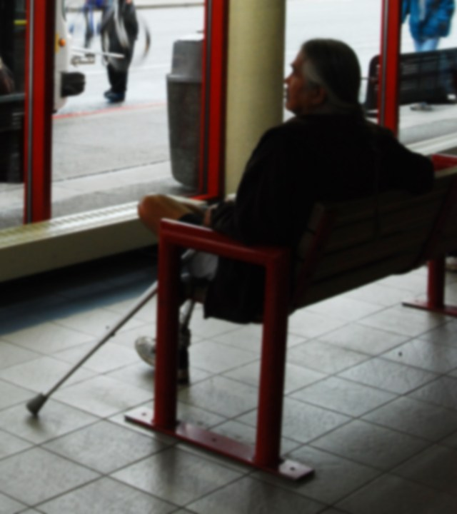 Male Native American sits with a crutch, waiting for a public bus