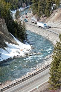 Semi Trucks and other vehicles travel along HWY 191 alongside the Gallatin River on the way to Big Sky.