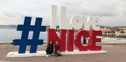 Annmarie McMahill and Jay Otto in front of a local welcome sign in Nice, France