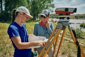 Haley Tupen and Katey Plymesser with monitoring equipment next to Yellowstone River