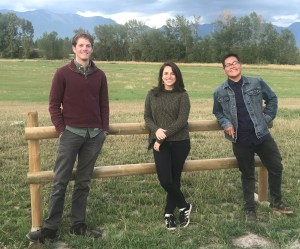 Transportation Fellows Vince Ziols, Naomi Fireman, and Nathan Begay in field with mountain view near Kalispell, Montana.