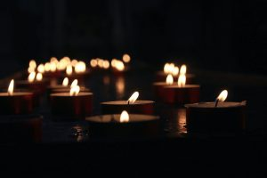 A group of candles burn in an otherwise dark church.