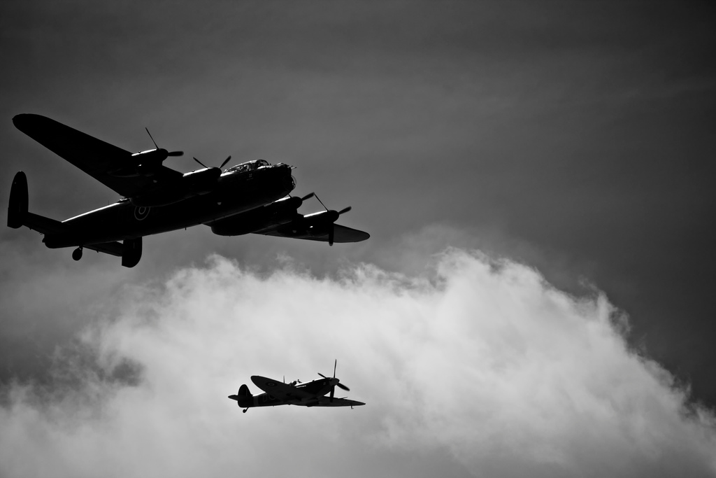Lancaster Bomber with a Supermarine Spitfire flying next to it.