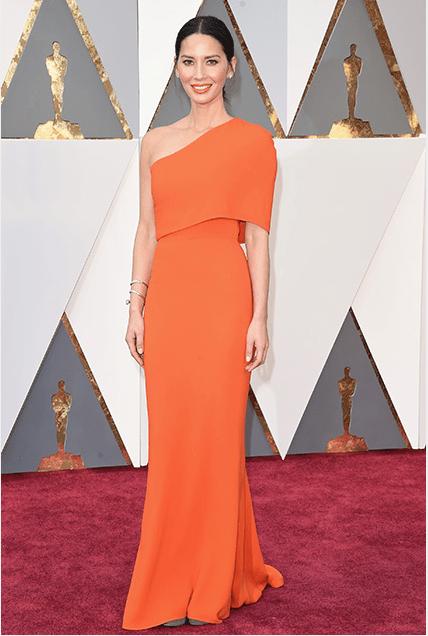 Olivia Munn in a bright orange gown.