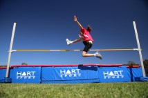 Young athlete jumping Right to left over a High Jump bar with arms raised