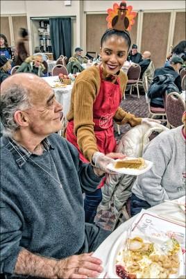 Thanksgiving volunteers serving the homeless turkey dinners