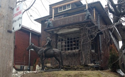 Front yard installation - statues of horse and rider, two balcony jaguars, and a pair of cowboy boots protruding .from the ground