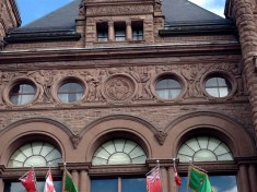 Carved stone frieze above arched doorway depicts Ontario's art, culture and industry.