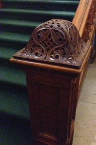 An ornately carved wooden newel post.