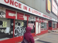 Honest Ed's last weekend - Heather checks out what's left in the windows (mostly farewell signs).