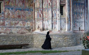 Nun walking in front of the painted walls of Humor monastery