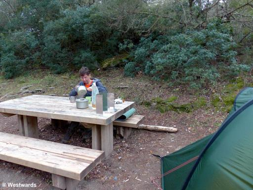 Hiker having breakfast at a picknick table besides a tent