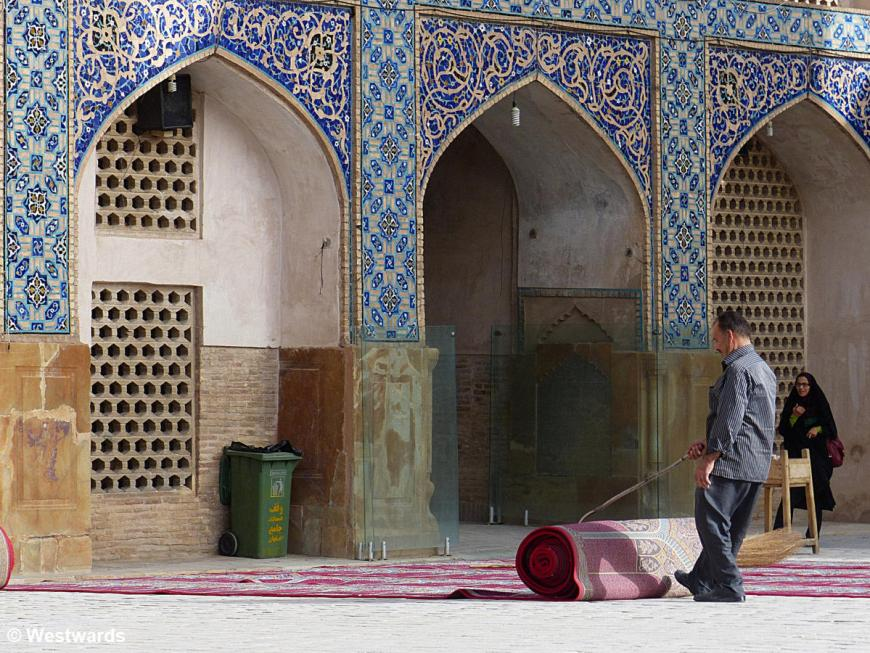 man rolling a carpet in a mosque courtyard