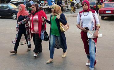 Three women with headscarfs walking on the street