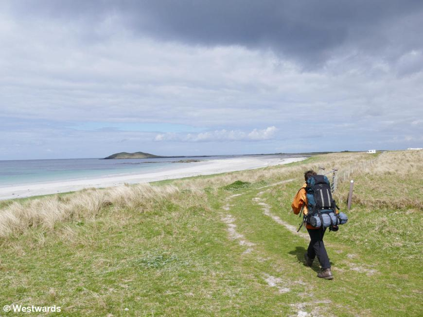 Woman hiking the Hebridean Way along the white beach in South Uist
