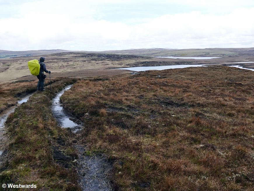 Woman hiking the Hebridean Way, in the moor near Harris