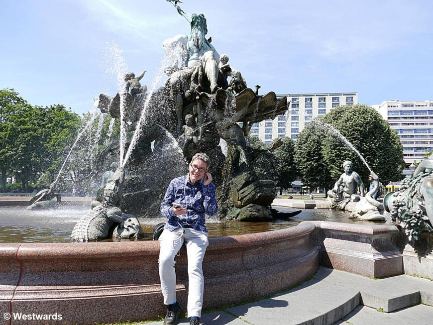 Woman with earphones in front of the Neptun fountain, on a self-guided walk through Berlin