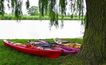 Four colorful kayaks lying on the gras