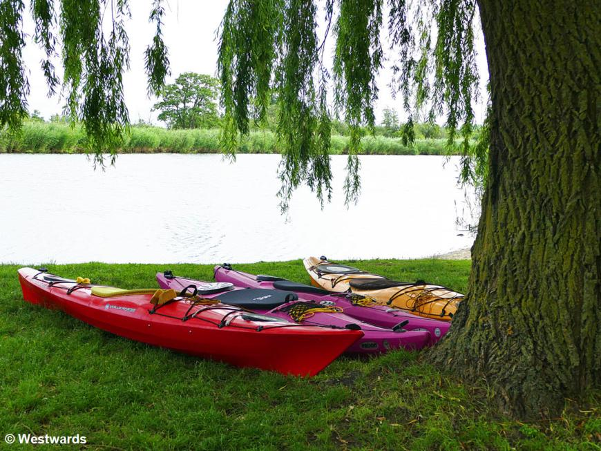 Four colorful kayaks lying on the gras