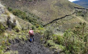 Hiker on a small muddy mountain path