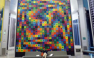 Natascha sitting on a couch in front of a huge Vasarely painting